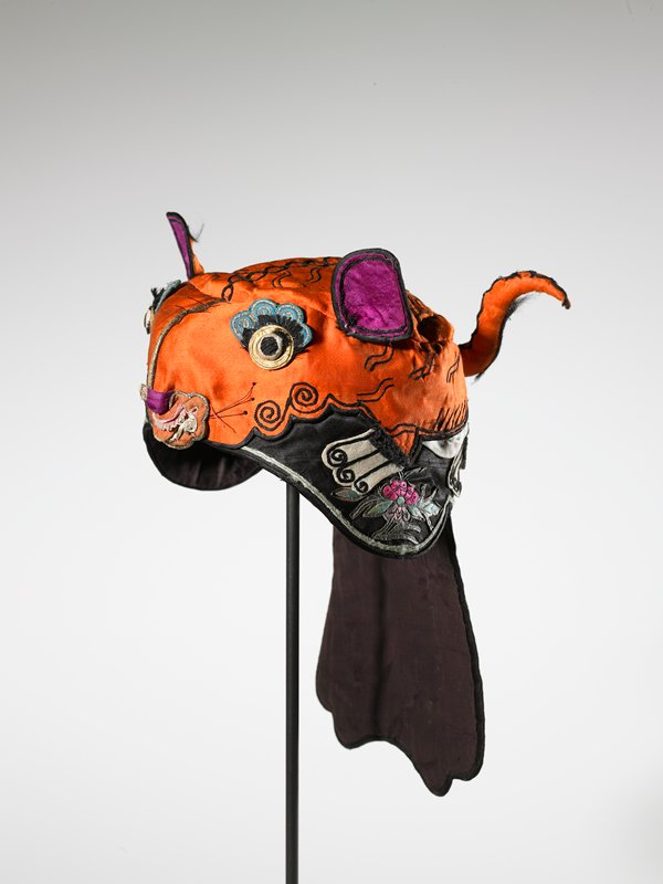 orange tiger's face at top and front with purple ears; small tiger's tail on back at top; black around sides and back with flowers; blue and white tail with pink lotus blossom and gold floral designs