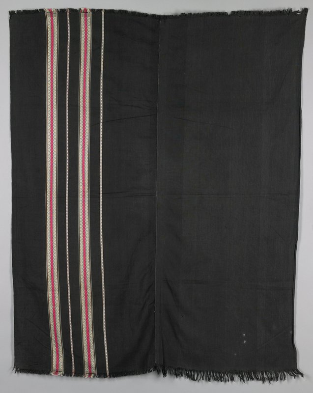 two black cotton panels joined at selvedge, one plain and one with two narrow and two wider vertical stripes in zigzag and diamond pattern in pink and white; fringe on both ends