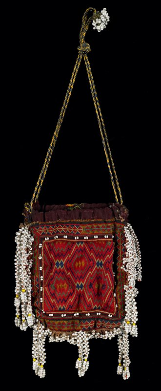 red with white beads; small drawstring bag completely covered with embroidery, both sides; white beaded fringe on three sides; braided drawstring, knotted with beads at end; diamond design on one side, zig-zag on other; lined