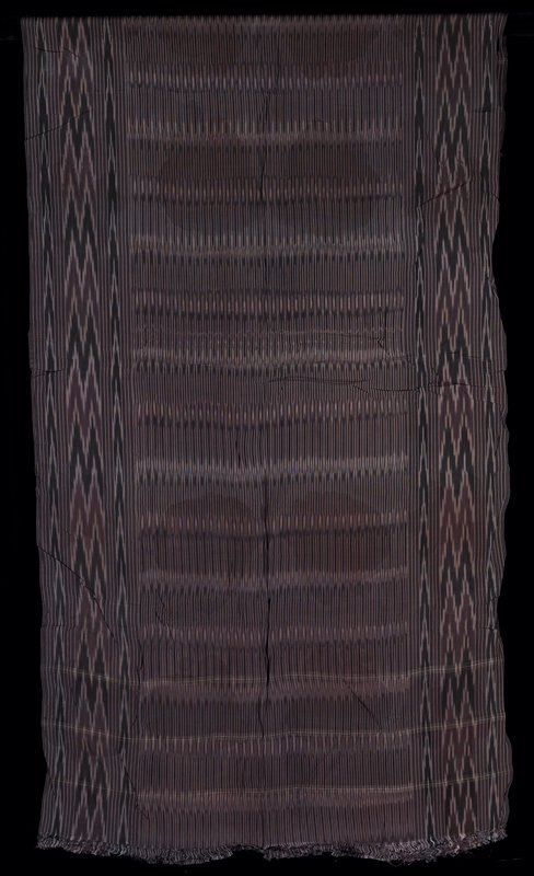 "long rectangular silk ikat with fringe on two ends; narrow horizontal stripes with wides ""thunderbolt"" pattern on horizontal borders; purple, black and white ?"