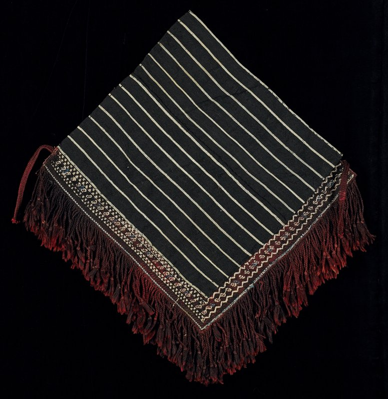#157 cotton label; stripped woven square in two pieces--black and white--with an attached woven band at right angle--white, blue, red and black--with knotted applied fringe; braided tie on opposite corners