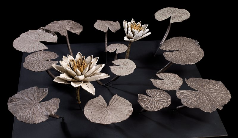 14 water lily leaves with one large flower and one smaller flower extending up from a black metal base; leaves and flowers detach from base