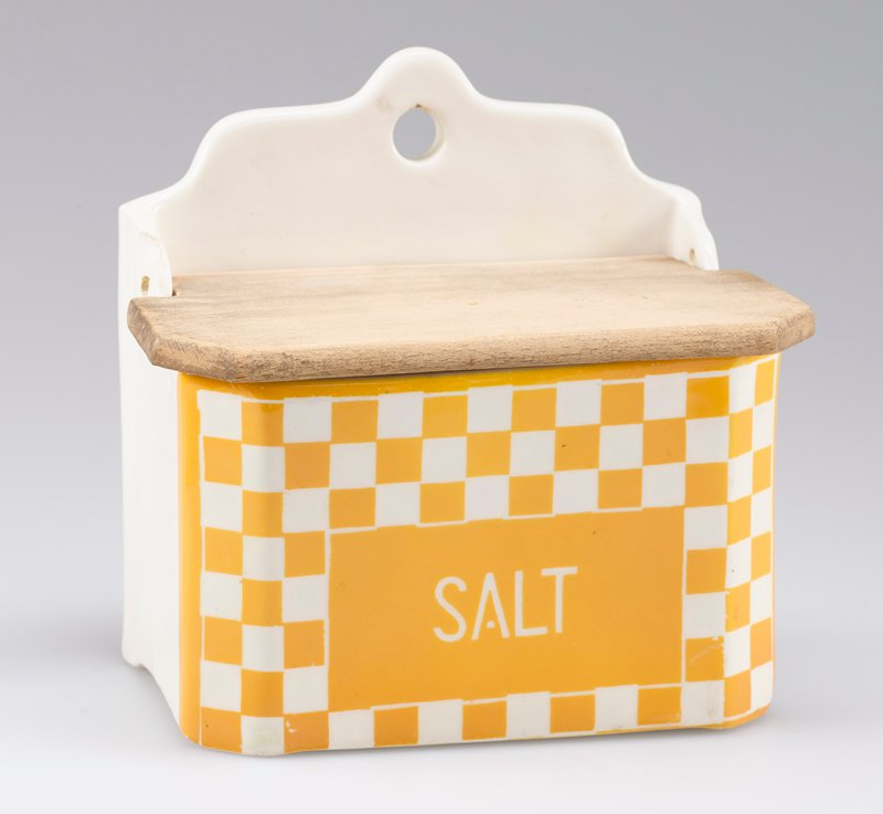 "small box with squared-off front corners; hanging hole on back; wooden cover; white porcelain decorated with yellow-orange checkerboard and ""SALT"" in white on front"