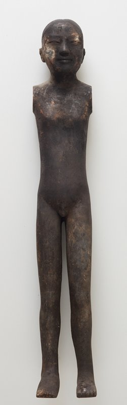 tall, long-legged male figure without arms; large, flat feet; nude; hair in small knot on top of head; black patina