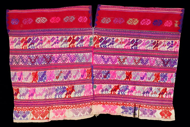"four woven panels with sides sewn together and center seams front and back embroidered together; alternating rows of narrow horizontal stripes and rows of animal and bird figures and geometrics; bottom has ""flounce"" of off-white; pink, purple and red with solid red yokes with geometric designs; neckline is vertical slits front and back"