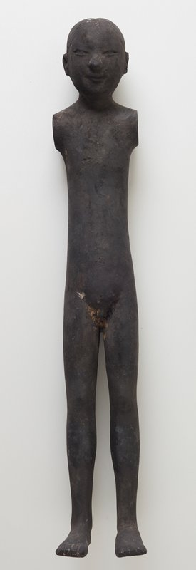 standing nude male figure; thin with long legs; flat feet; arms lost; hair in small knot at top of head; black patina