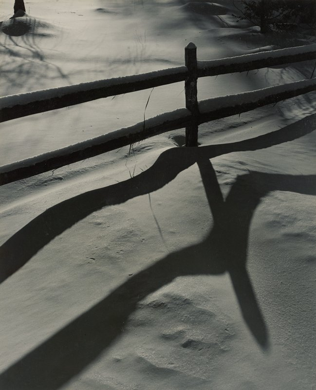 fence in the snow, casting a shadow of wavy lines