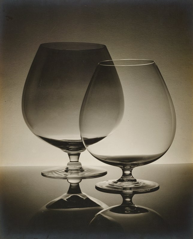 two glass brandy snifters on a reflective surface