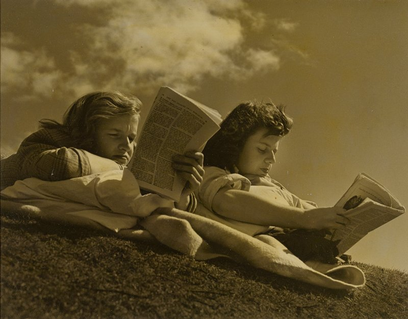two young women, lying on their stomachs, reading magazines, on the slope of a hill; clouds overhead