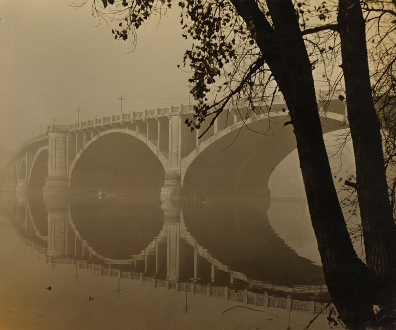 two tree trunks and tree branches at R; long bridge with arches, reflected in water; dull sky