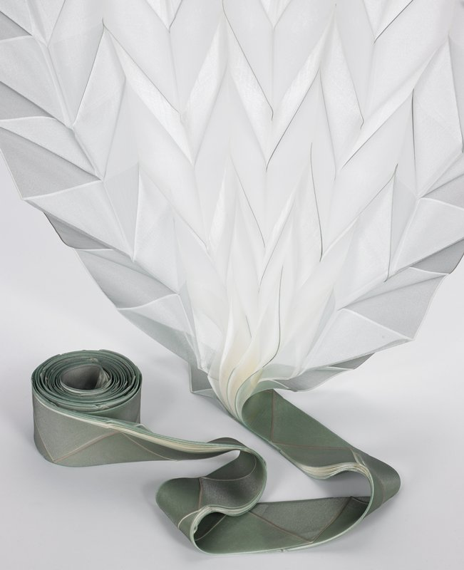 light moss green that fades to cream color; shape is created by two-sheet paper patterns between which was laid plain polyester fabric, heat- pressed; folds and transfer printed in different colors by hand; all edges serged; three dimensional origami pleats