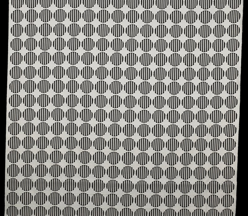 "plain woven off-white ground with dark flecks with supplementary patterns (?); 3 1/4"" black and white striped circles; top and bottom machine serged by company for display panel"
