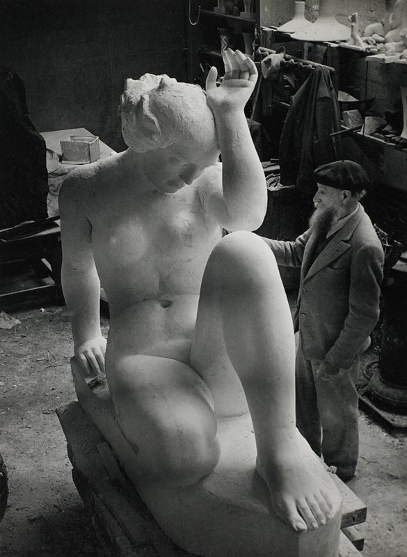 bearded man at R wearing a suit and a beret, facing a large sculpture of a seated woman with one knee up