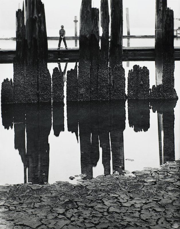 little boy with feet apart, standing on a dock, fishing, viewed between weathered wood posts in water, cracked shoreline ground in foreground