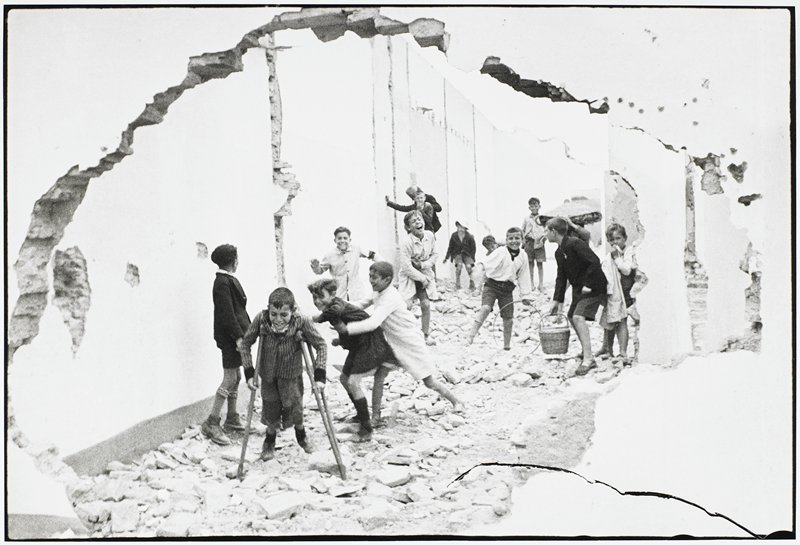 children playing in rubble seen through a hole in the foreground wall; one child on crutches, a second with a hoop; fifteen figures visible