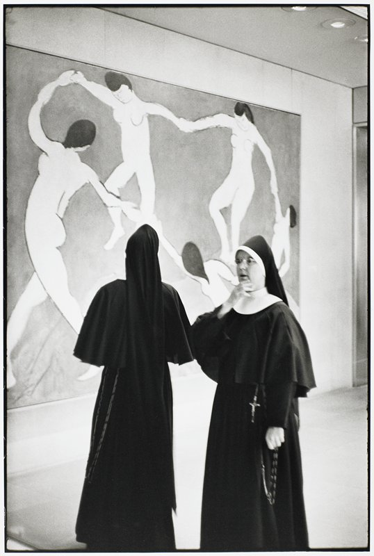 two nuns in front of a painting of nude women in a circle