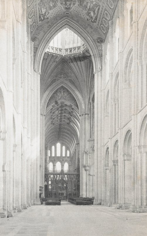 view down the aisle of a pointed arch Gothic style cathedral; fragments of ceiling decoration visible; Gothic screen at end of aisle