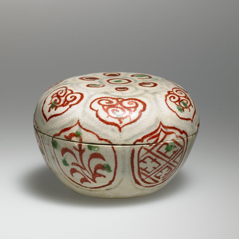 small container with concave bottom; rounded sides with subtle ribs; flat top; white with pale blue, red and green organic and geometric cartouche designs