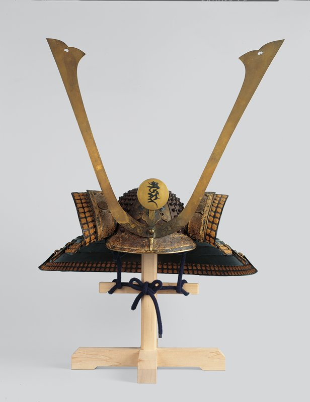studded helmet with short visor at front and four-tiered, wide spreading laced neck guard; curving face protectors with decorated buckskin, studs, and crests; heraldic metal disc with Sanskrit characters for the Buddhist deity Fudo; pair or thin, bladelike metal kuwagatas at front center with heart cutouts; neck guard held together with green ties; ochre colored knots around borders; has wooden stand