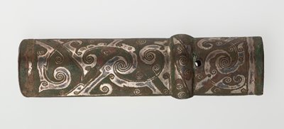 The design of highly stylized dragons, inlaid with silver, appears on the two main areas of this butt cap. The encircling rounded band carries the volute and angle pattern poplular in Huai time. Like 50.46.5, this cap is oval in cross-section. Butt caps of this type, designed for lance hafts, are quite rare. Patina reddish-brown with small areas of green. Bronze with silver inlay.
