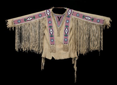 hide shirt with fringe on arms and neckpiece and short fringe on bottom; beaded strips on sleeves and over shoulders; triangular beaded flaps at neck, front and back; pink beaded ground with geometric multicolored designs