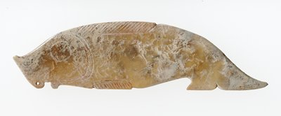 low relief pendant in form of fish, simplified profile; curved slope tail; very small perforation at lower lip; incision to suggest fin and general features, both sides identical; pale light brown translucent jade, partially calcified; traces of red pigment on the back side