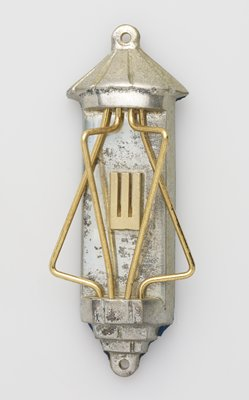 silver architectural-like element with four pieces of gold twisted wire, in a rough star of David, surrounding the Hebrew letter Shin.