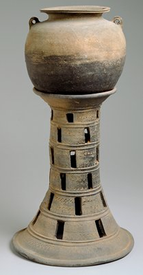 ceramic jar with stand; round body jar with flared rim and two small handles at upper shoulder; stand with flared base and rim, tapered body to rim, open through middle, six band decoration with staggered open rectangles cut out off each band; unglazed. Three Kingdoms Period (Kaya).